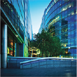 Image of office buildings with green trees on a blue-sky day.